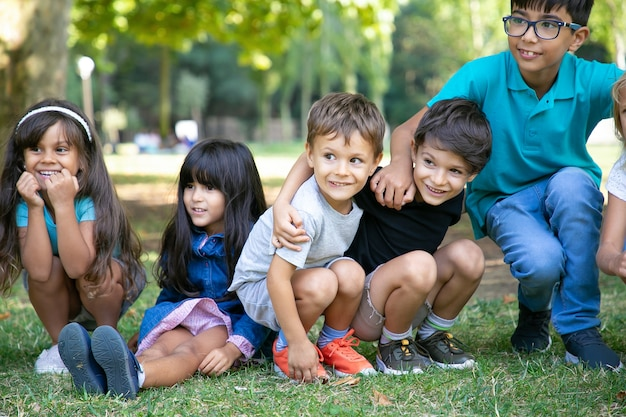 Cheerful kids sitting and squatting down on grass, hugging each other, looking away in excitement. kids play or entertainment concept