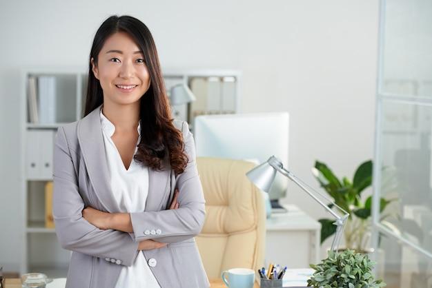 組んだ腕を持つオフィスでポーズをとって陽気な韓国ビジネス女性