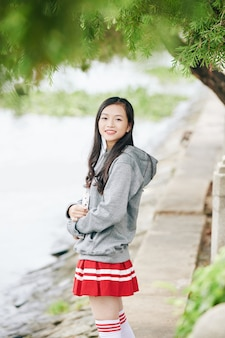 Cheerful korean schoolgirl in skirt and hoodie holding students book and smiling
