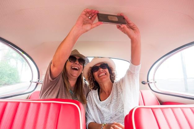 古い赤いビンテージ車の中で現代のスマートフォンを使った陽気な女性の白人と自撮り