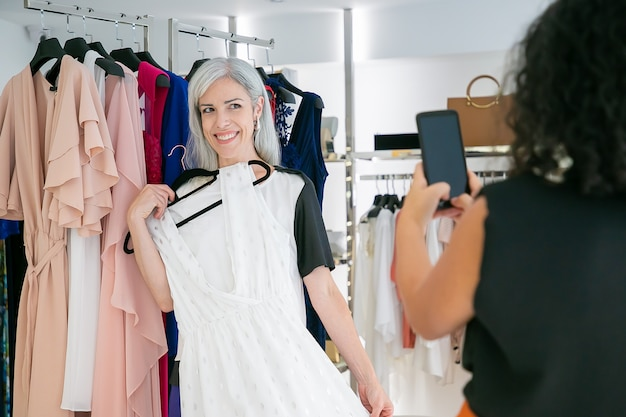 Веселые дамы наслаждаются покупками в магазине модной одежды вместе, держат платье и фотографируют на мобильный телефон. потребительство или концепция покупок