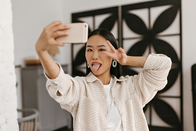 Cheerful lady in beige jacket shows v-sign and takes selfie on kitchen