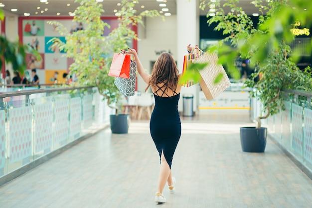 カラフルな買い物袋を運ぶ陽気な女性。魅力的なブルネットは満足しているように見えます
