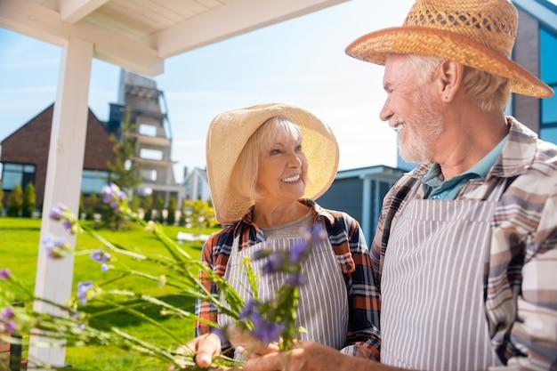 元気な女性。彼女の愛情のある思いやりのある夫を見ながら笑顔の素敵な帽子をかぶっている陽気なおばあさん
