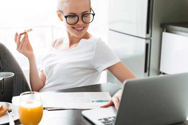 Cheerful lady eating bread with jam and using laptop