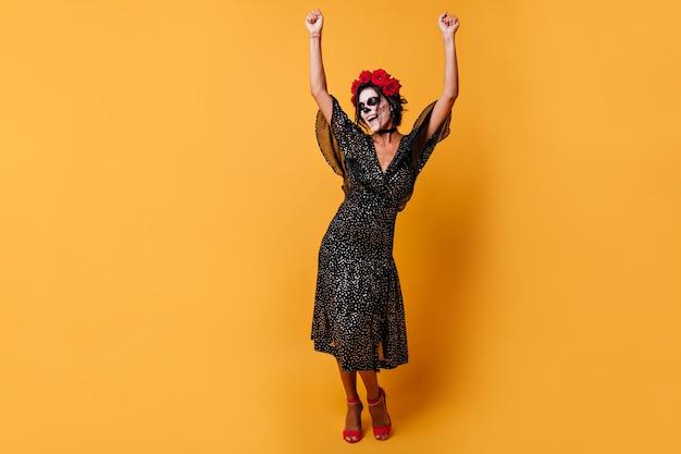쾌활한 아가씨는 팔을 위로 들고 감정적으로 춤을 춥니 다. 검은 머리와 할로윈 복장에 장미 왕관 모델의 초상화.