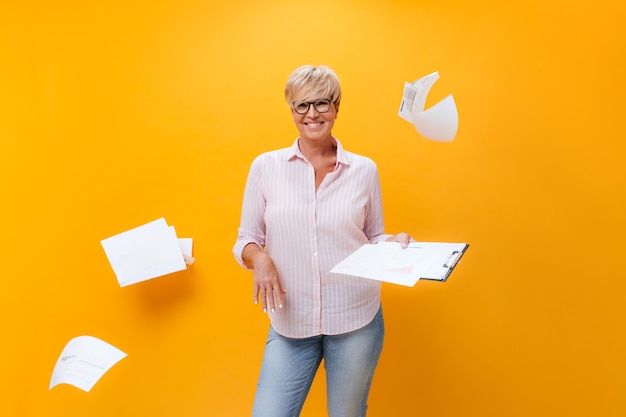 Cheerful lady in eyeglasses, shirt and jeans poses with paper sheets