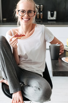 Cheerful lady in glasses sitting with bread and cup of tea in kitchen