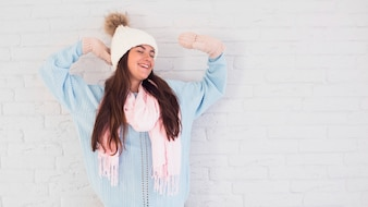 Cheerful lady in mittens, bobble hat and scarf with upping hands