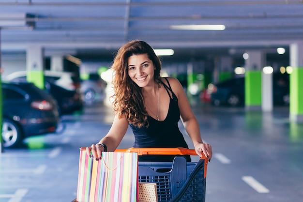 Веселая дама в стильном черном платье несет красочные сумки на стоянке возле автомобиля.