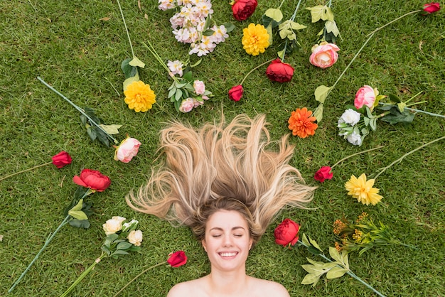 Cheerful lady lying on grass between flowers