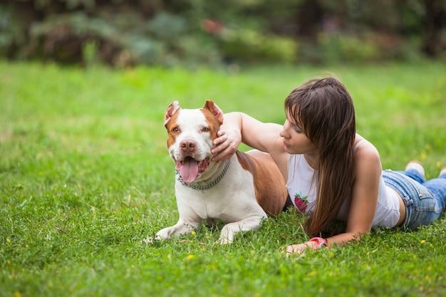 Веселая дама лежит на траве с собакой