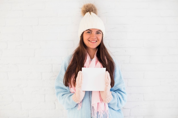 Cheerful lady in mittens, bobble hat and scarf with square paper