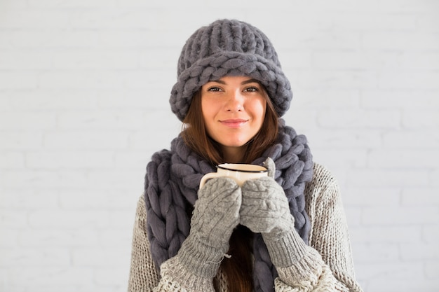 Cheerful lady in mittens, hat and scarf with cup in hands