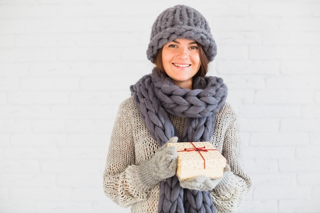 Cheerful lady in mittens, hat and scarf with present box