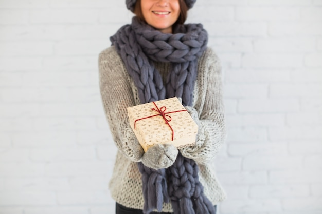Cheerful lady in mittens and scarf showing present box