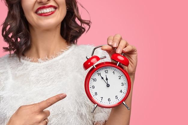 Веселая дама указывает на будильник с без пяти двенадцать