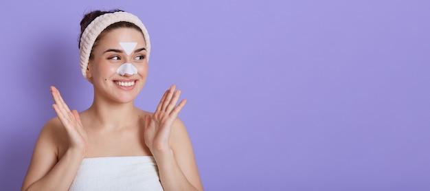 Жизнерадостная дама позирует изолированно над сиреневой стеной с белыми наклейками на коже на носу и лбу, процедура очищения, счастливая женщина смотрит в сторону, копирует пространство для рекламы, разводит руку, как будто хочет хлопать в ладоши.