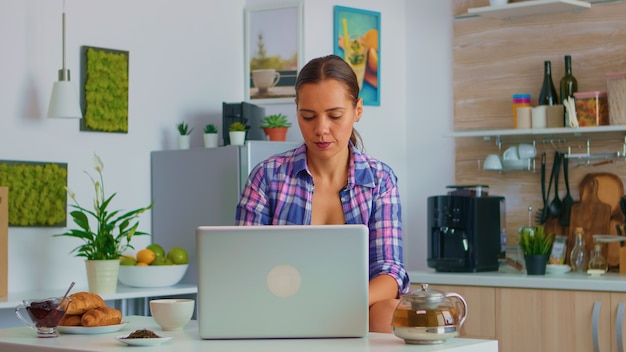 居心地の良いキッチンで朝食時に緑茶をすすり、ラップトップコンピューターで郵送する陽気な女性。インターネット技術を備えたデバイスを使用して自宅で作業し、朝にガジェットを閲覧、検索します。