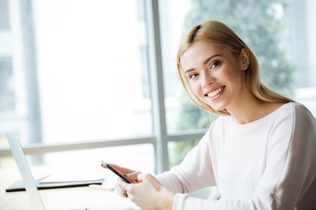 Веселая дама сидит в офисе коворкинг в чате по телефону.