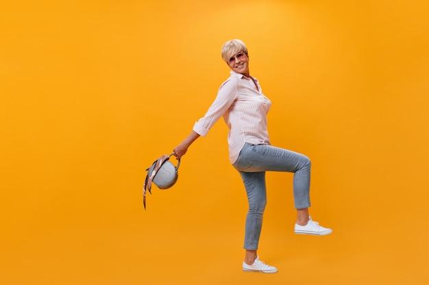 Signora allegra in abito street style tiene borsetta su sfondo arancione