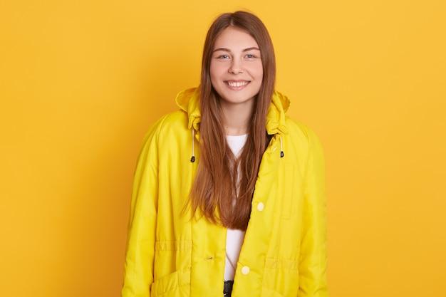 明るい黄色のジャケットを着ている陽気な女性、女性は長く美しい髪を持ち、機嫌が良く、幸せな表情で立っています。