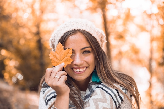 Cheerful lady with autumn leaf