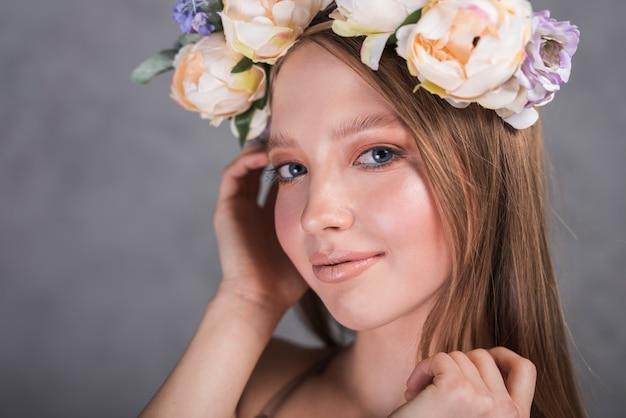 頭の上の花を持つ陽気な女性