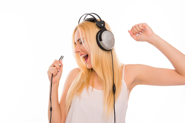 Веселая дама в наушниках слушает музыку и поет