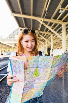 Cheerful lady with map on platform