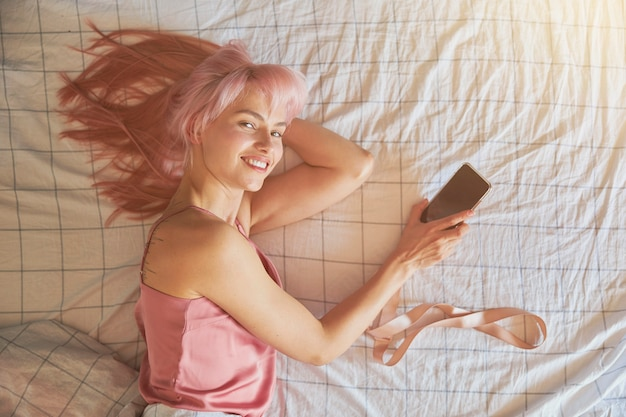 분홍색 머리를 한 쾌활한 여성이 편안한 침대에 빈 화면이 있는 휴대전화를 들고 있습니다