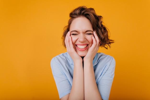 눈으로 웃고 반짝이는 물결 모양의 머리를 가진 쾌활한 아가씨가 닫힙니다. 파란색 옷에 웃는 백인 여자의 근접 실내 초상화.