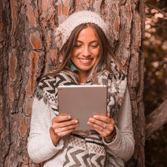 Cheerful lady with tablet near tree