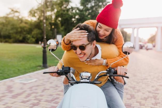 Signora allegra con manicure alla moda gioca con i capelli del ragazzo mentre guida lo scooter
