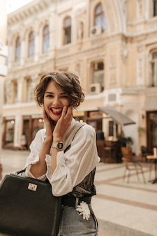 Cheerful lady with wavy hair in blouse with black lace laughing at street. trendy lady in jeans with handbag posing in city.