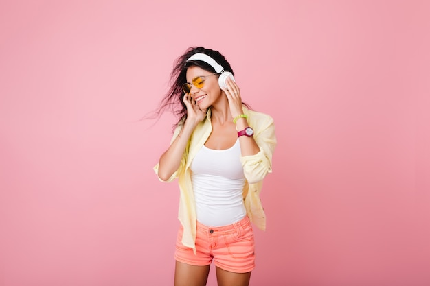 Cheerful latin woman in white tank-top and pink shorts listening music with eyes closed. spectacular black-haired asian female model in cotton jacket relaxing in headphones.