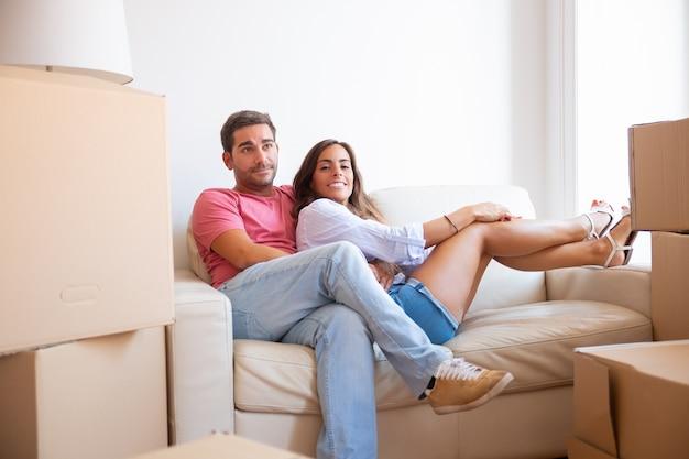 新しいアパートの段ボールのパッケージの中でソファに座っている陽気なラテン系の若いカップル、