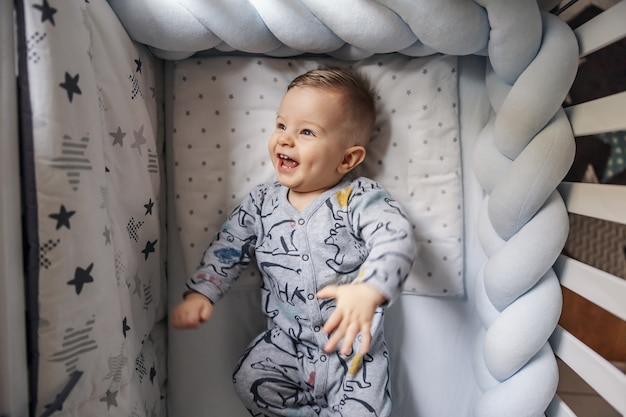 Cheerful laughing blond little baby boy with beautiful blond eyes rolling in his crib. morning time.