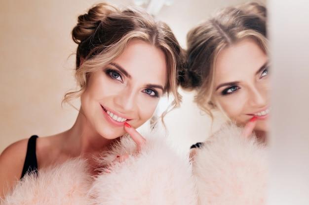 거울 옆에 화장을하는 동안 포즈를 취하는 귀여운 헤어 스타일로 쾌활한 웃는 소녀. 밝은 배경에 성실한 미소로 서 트렌디 한 코트에 즐거운 곱슬 젊은 여자의 초상화