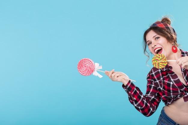 오른쪽을 보여주는 막대 사탕과 파란색 표면에 포즈 복고풍 옷에 쾌활한 웃음 예쁜 젊은 여자