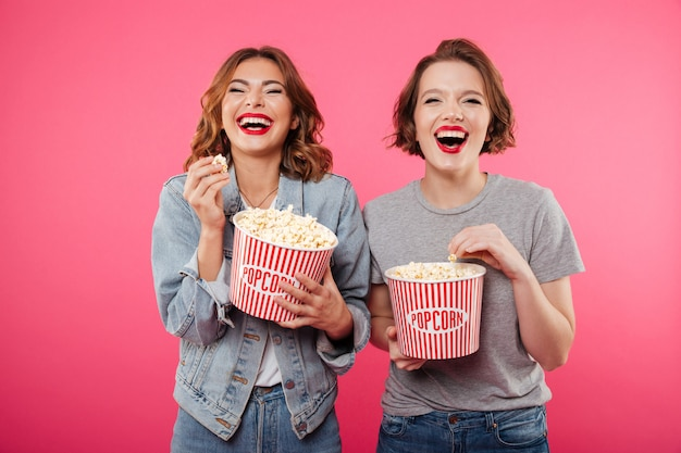 Cheerful laughing women eating popcorn watch film.