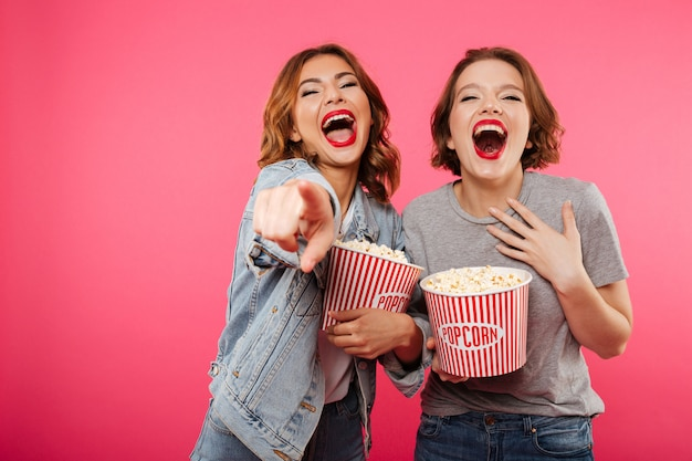 Cheerful laughing women friends eating popcorn watch film pointing.