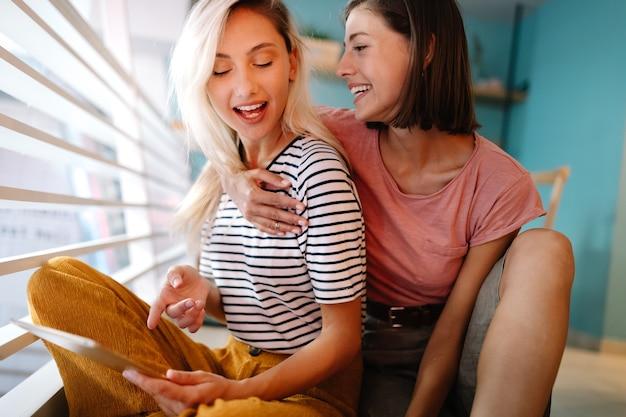 Веселые лесбиянки страстно обнимаются и веселятся вместе