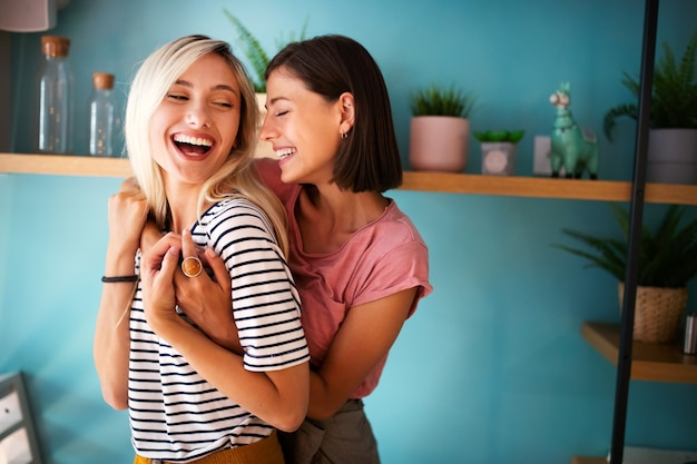 명랑한 레즈비언 여성은 열정적으로 포옹하고 함께 재미를 느낍니다.