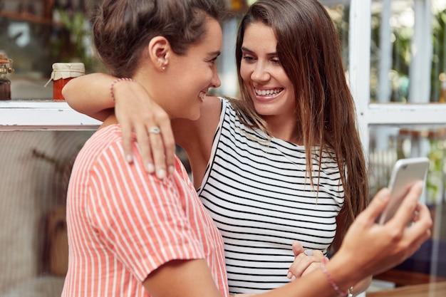 陽気なレズビアンは情熱的に抱き合って一緒に楽しみ、写真や娯楽のために現代の携帯電話を使用し、同性愛関係を示します。 samesexカップルは電子デバイスを使用します