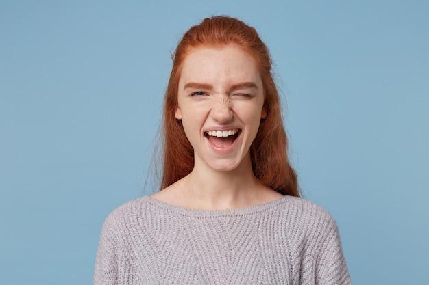 陽気な気さくな赤毛の少女、カメラにウィンク