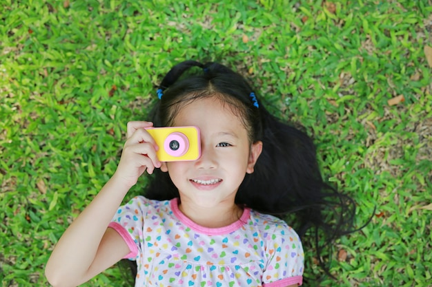 Cheerful little asian girl takes photo with colorful digital camera lying on green lawn