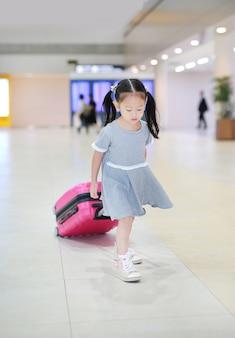 空港で荷物を持って歩く陽気な小さなアジアの女の子