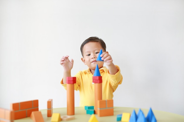 Cheerful little baby boy playing a colorful wood block toy on table .