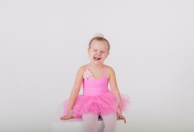 Cheerful little ballerina in a pink dress with a tutu skirt sits on a white wall
